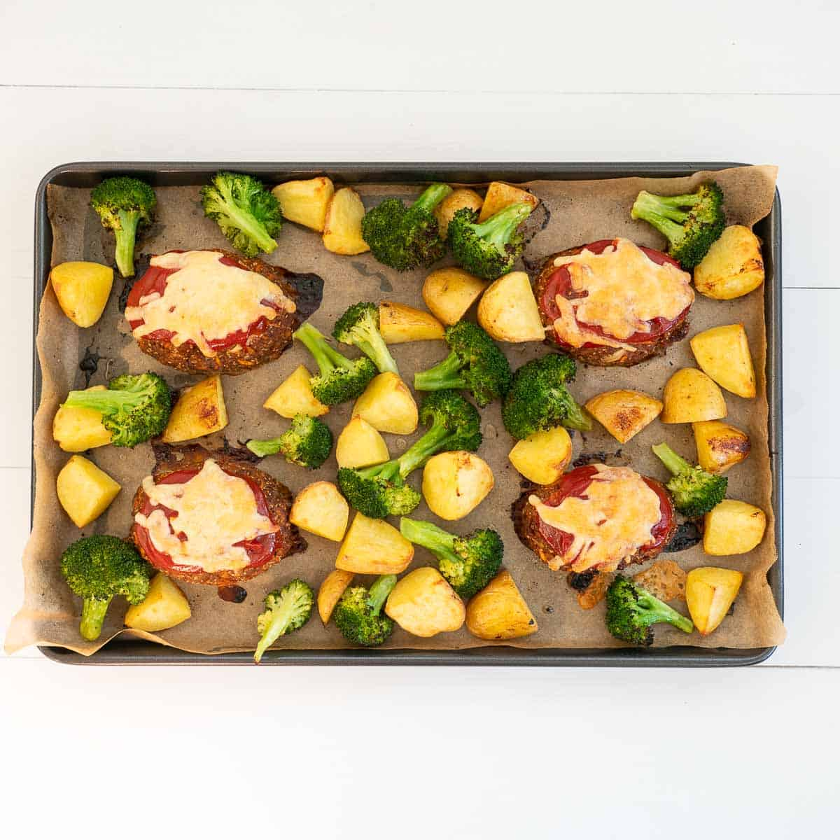 4 mini meatloaves toped with melted cheeseon an oven tray roast potatoes and broccoli