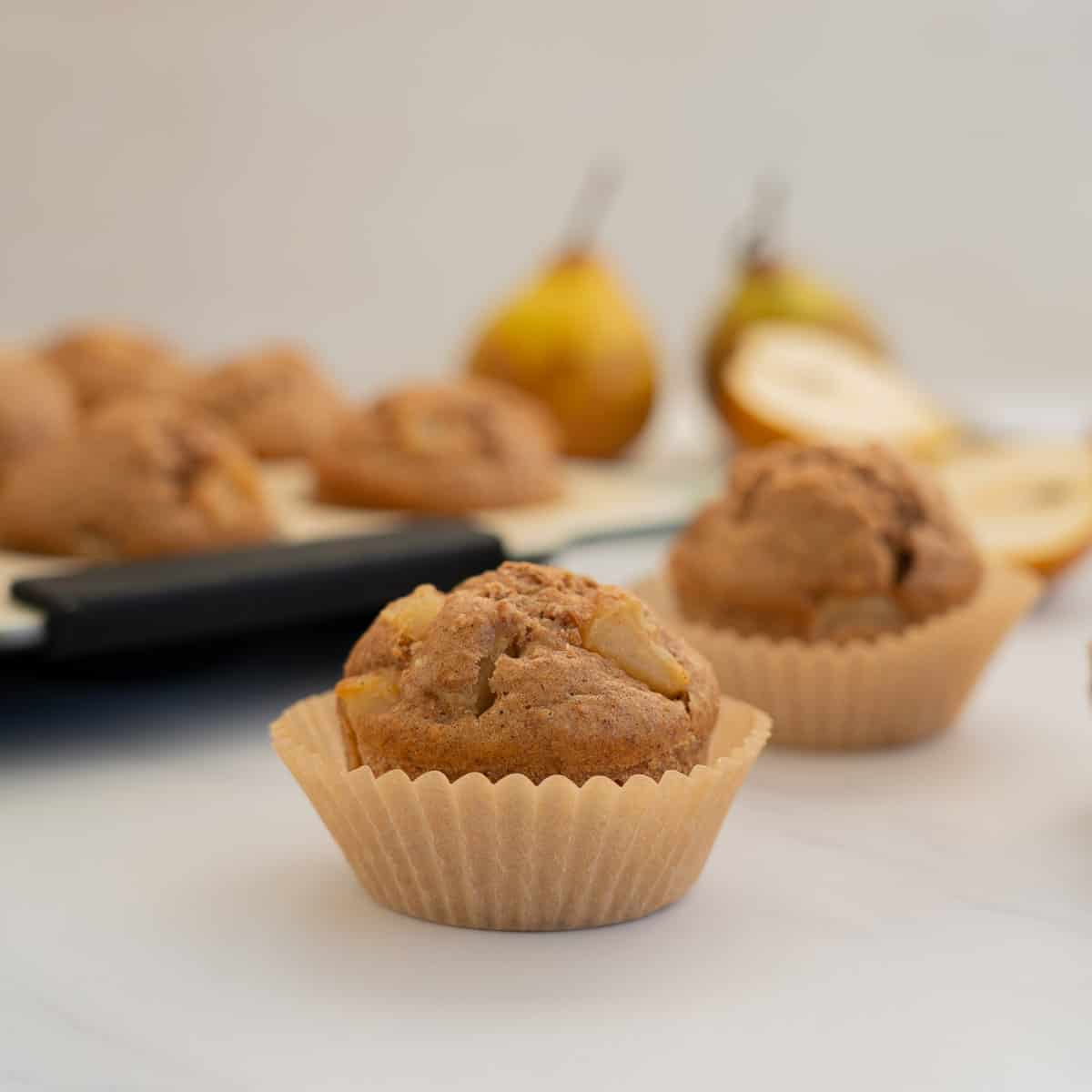 pear muffin in a muffin case on a marble bench top with a sliced pear in the background
