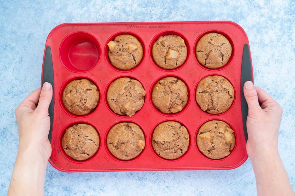 11 cooked muffins in a 12 cup red silicone muffin tray, tray held on either side by a woman's hands