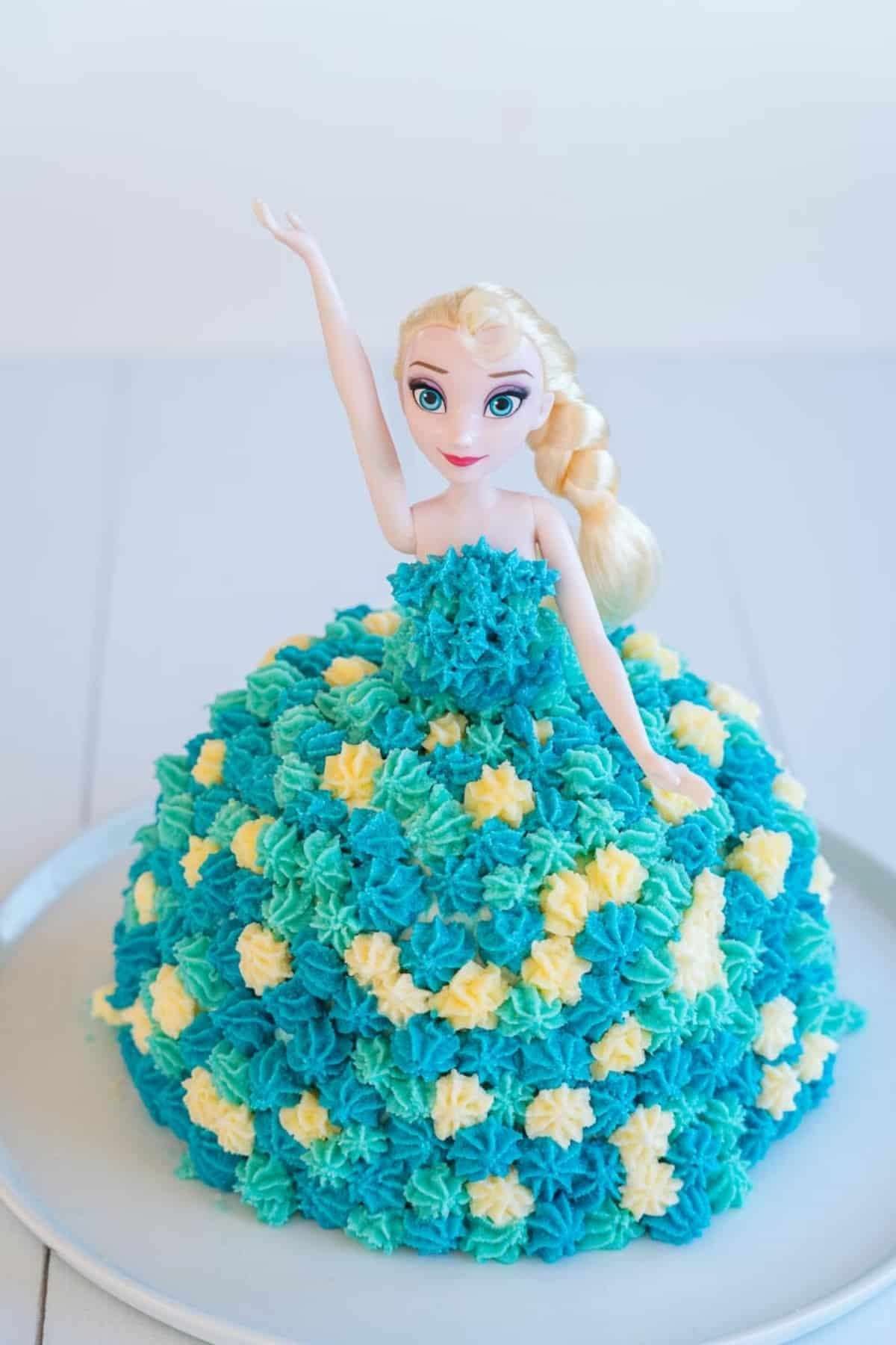 Birthday cake topped with an Elsa Doll, decorated with butter cream to look like a dress