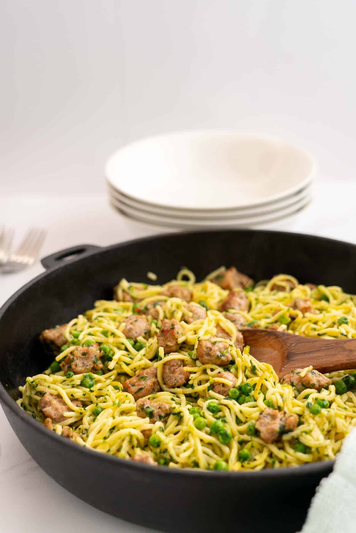 Golden Fried Spaghetti in a large skillet with sausage peas and spinach, serving bowls and cutlery in the background