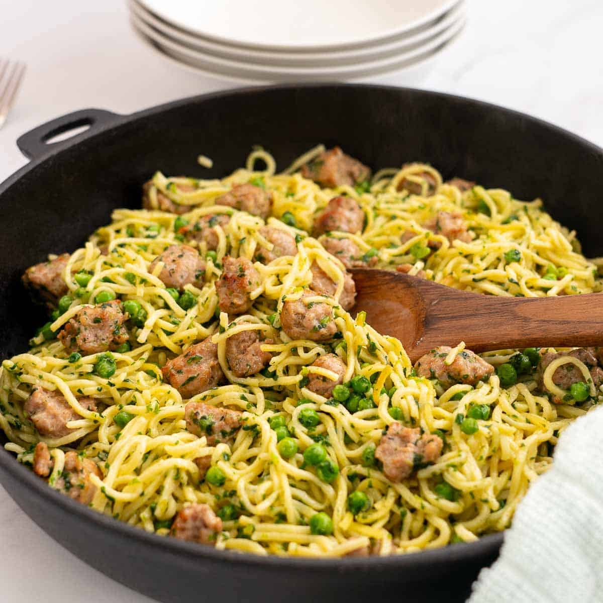 golden fried spaghetti in a large skillet with sausage peas and spinach
