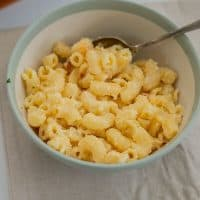 a bowl of mac and cheese sitting on a placemat with a spoon