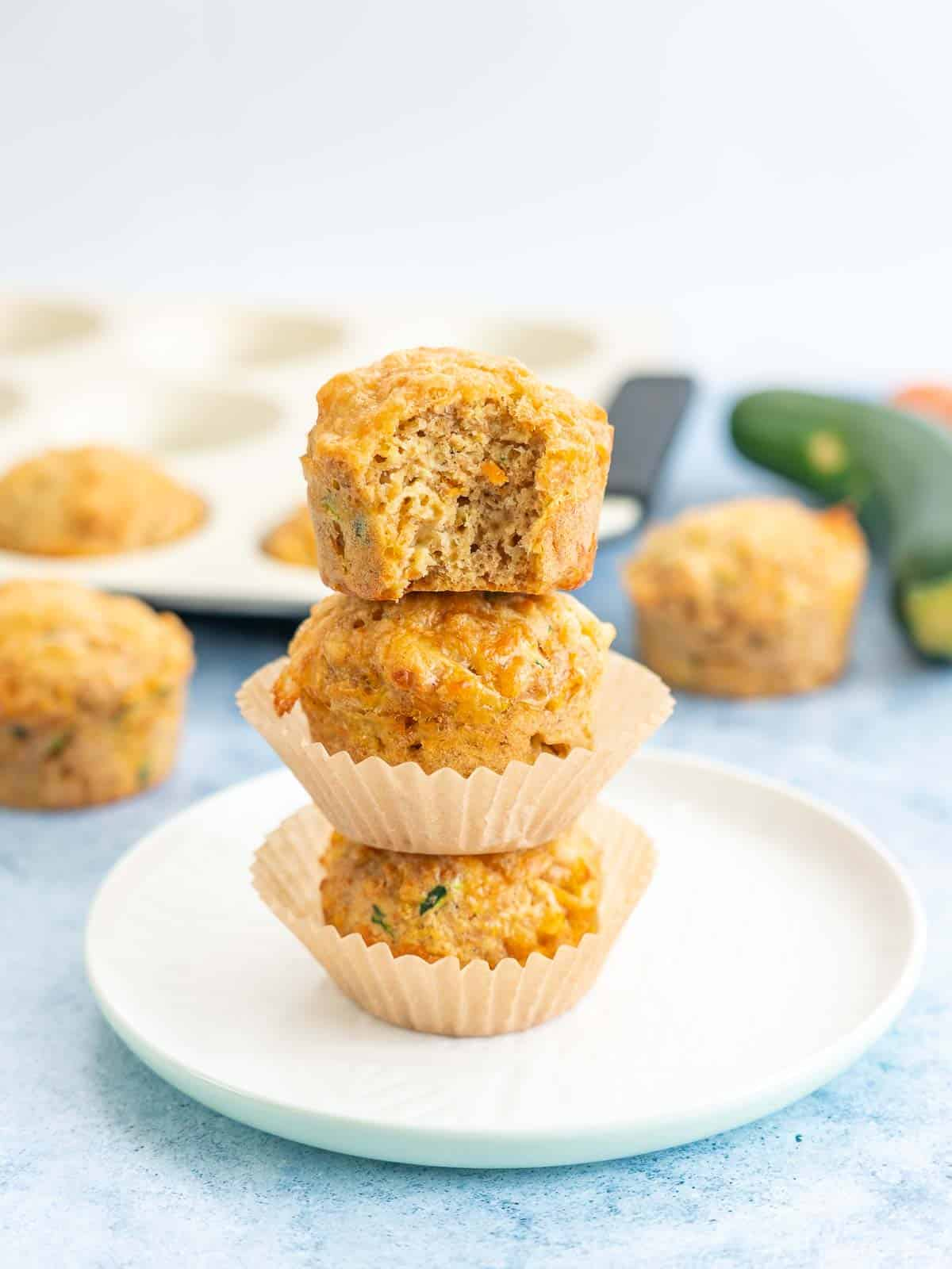 3 savoury muffins staked on top of each other, muffin tray and vegetables in the background
