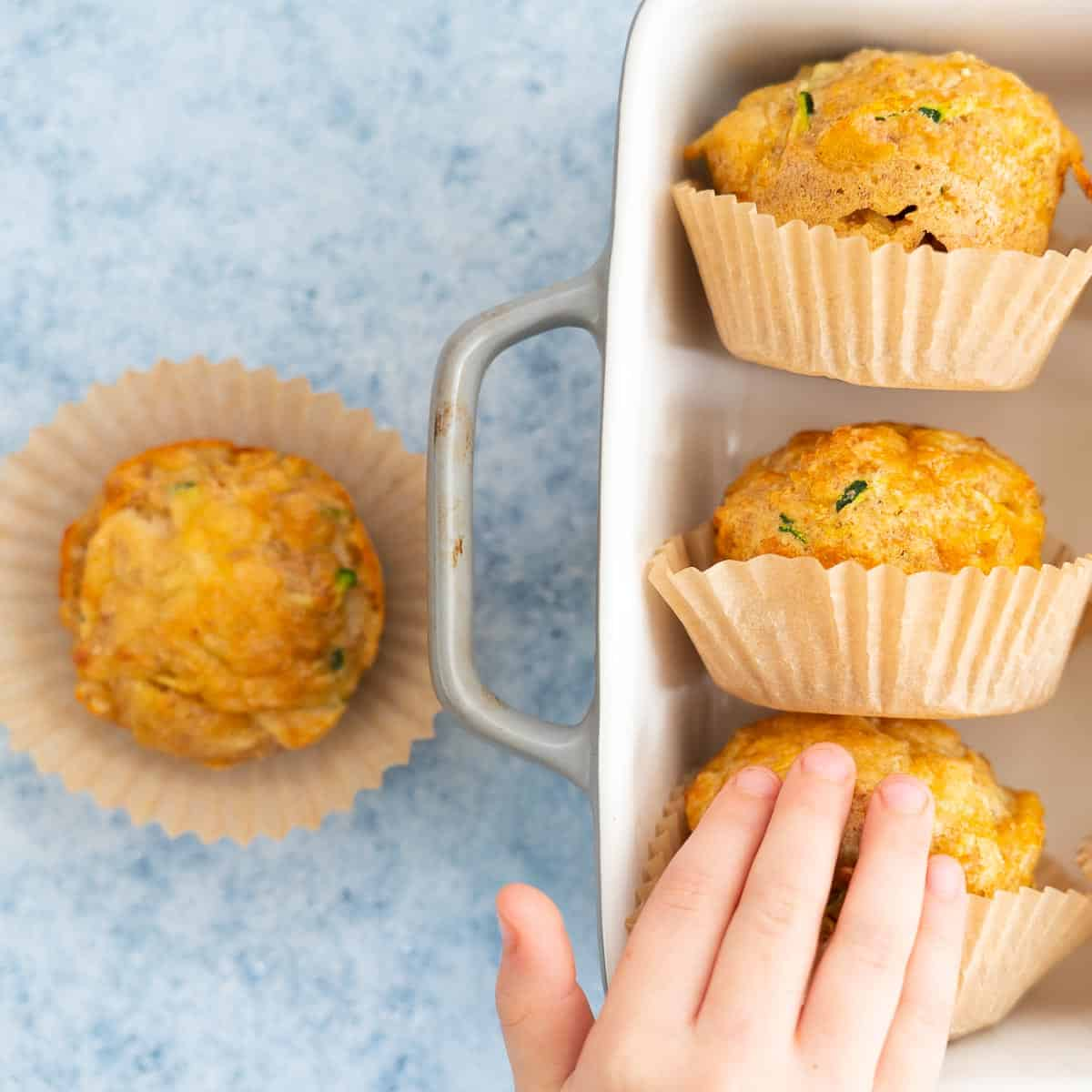 A child's hand reaching for 1 of 4 vegetable muffins in muffin cases