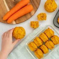 8 carrot muffins in a container with a child's hand reaching for a muffin