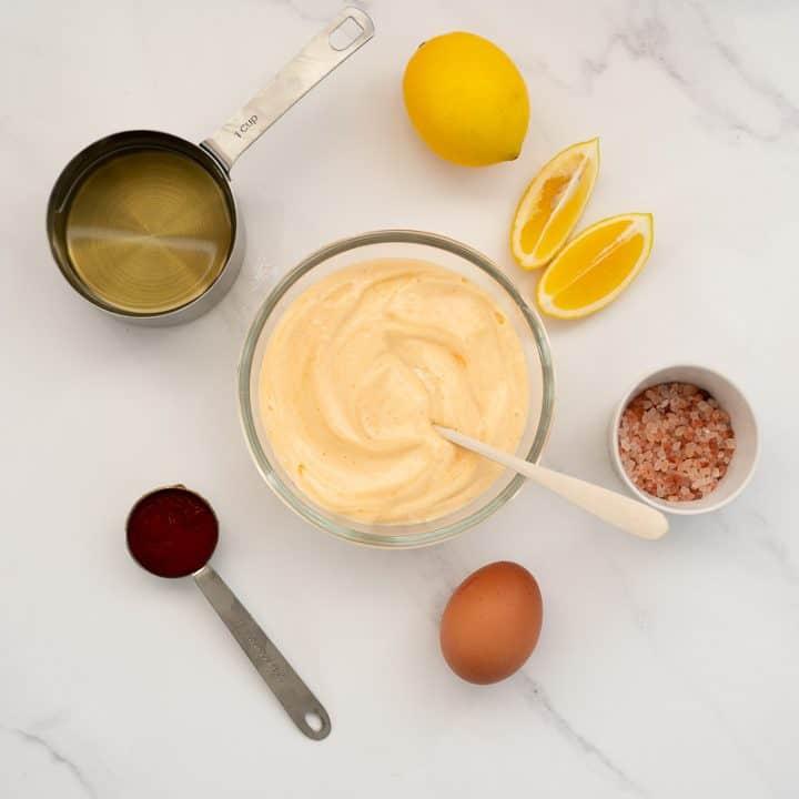 glass bowl of sriracha aioli surrounded by ingredients (oil, lemon, sriracha, salt, egg)