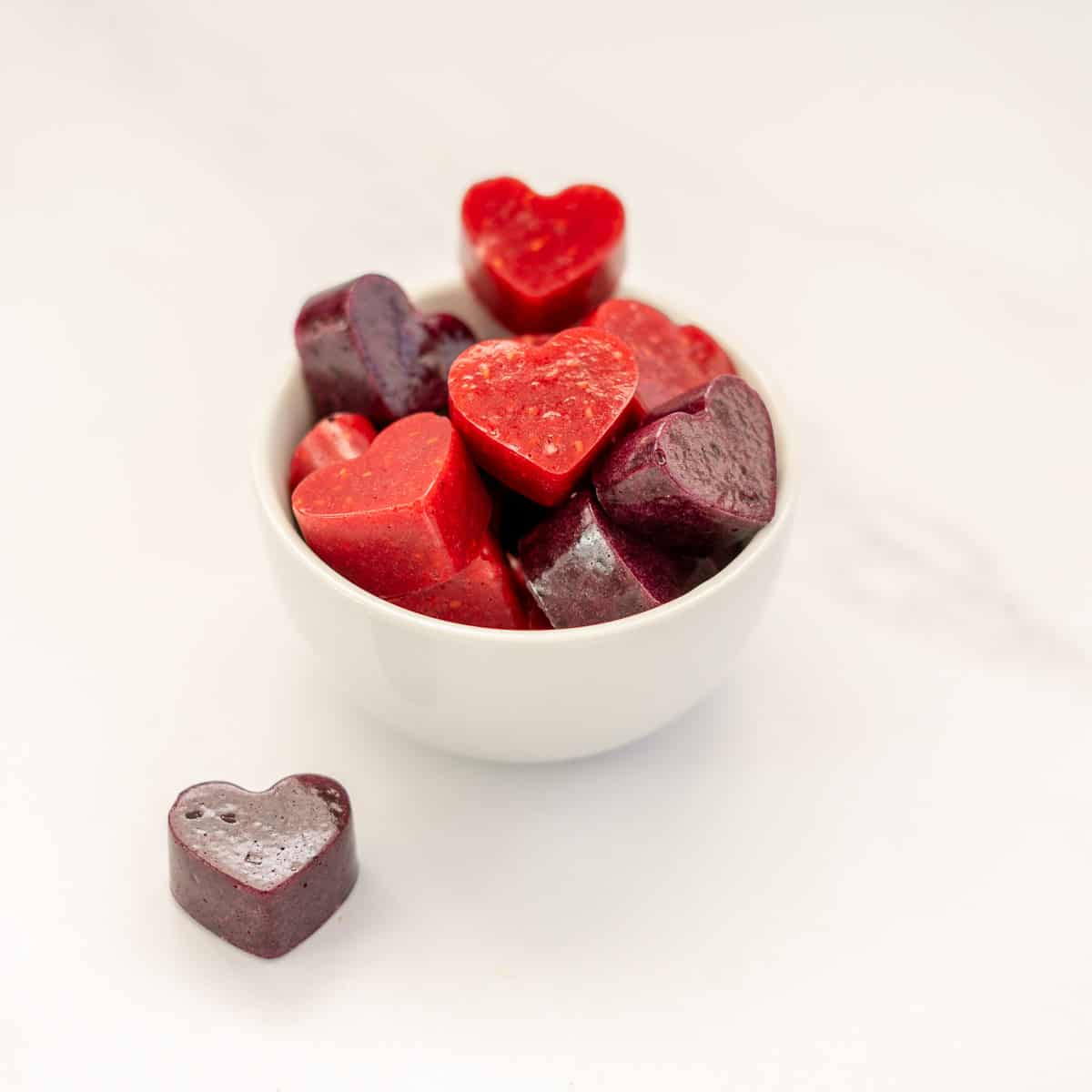 red and purple heart shaped fruit gummies in a white bowl
