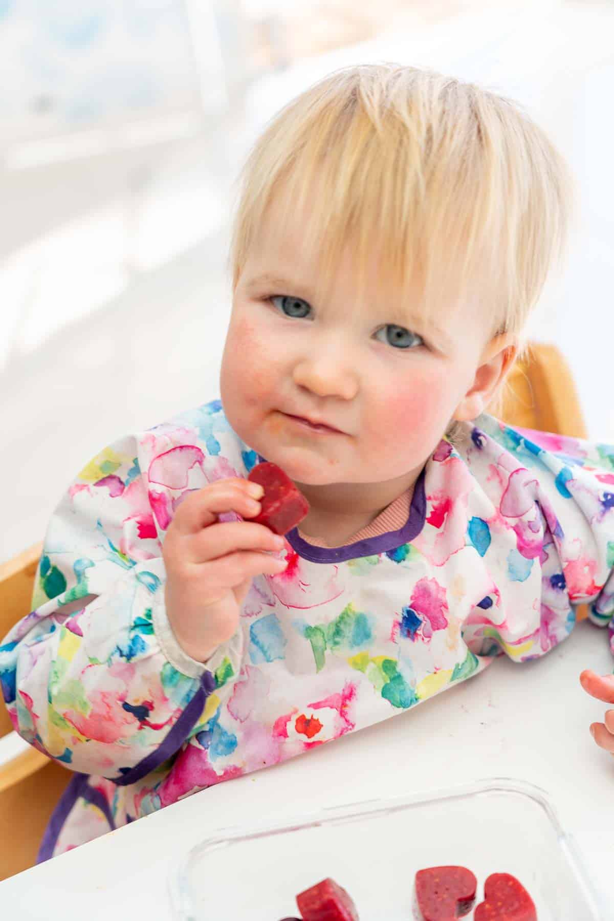 toddler in a colourful bib eating a fruit gummy