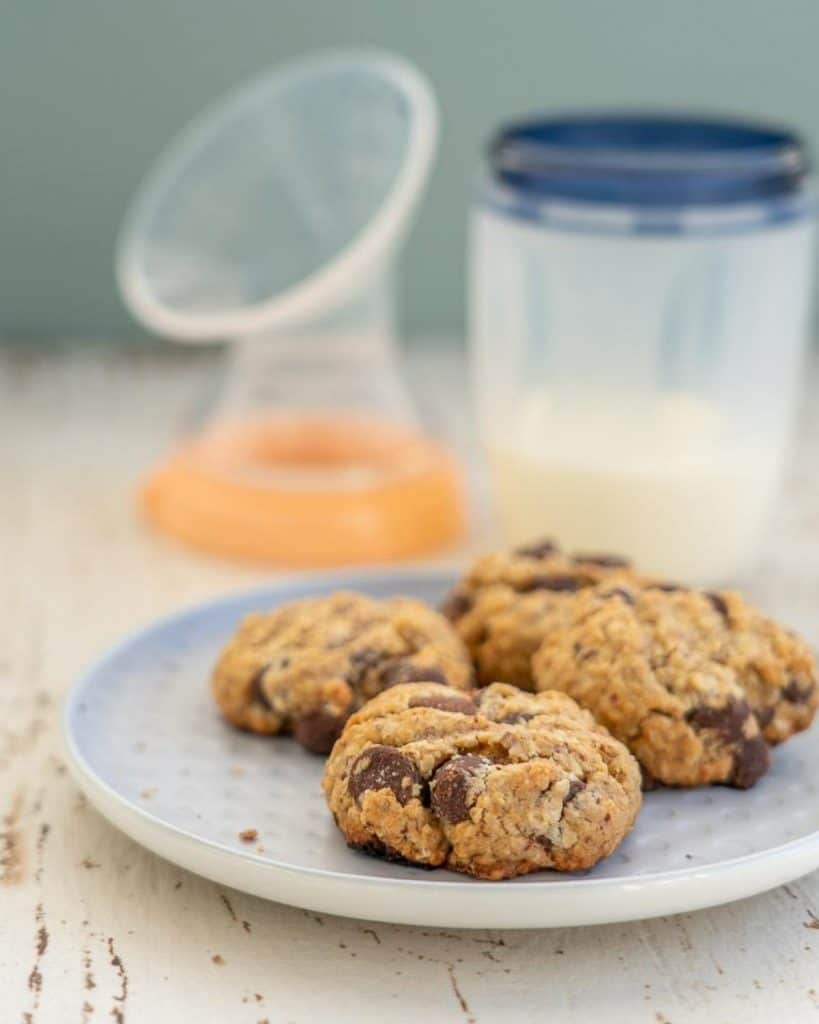 plate of choc chip oatmeal lactation cookies sitting in front of a breast pump