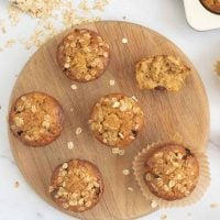 top down shot of oatmeal muffins on a round wooden tray with a scoop of rolled oats