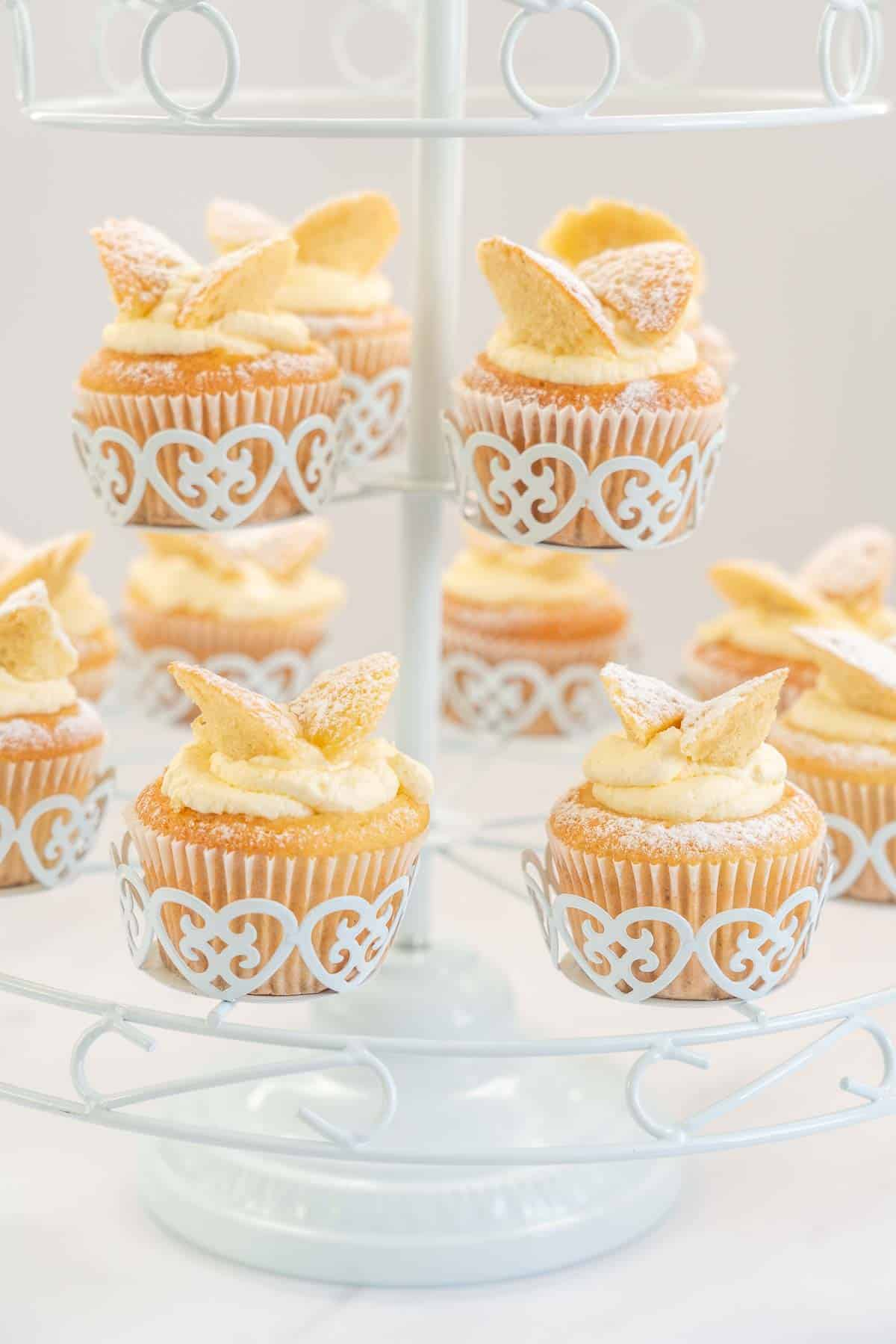 A dozen butterfly cupcakes in a white wire cupcake stand