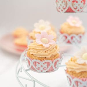 dairy free cupcakes frosted with pink icing and a flower in a white cupcake holder