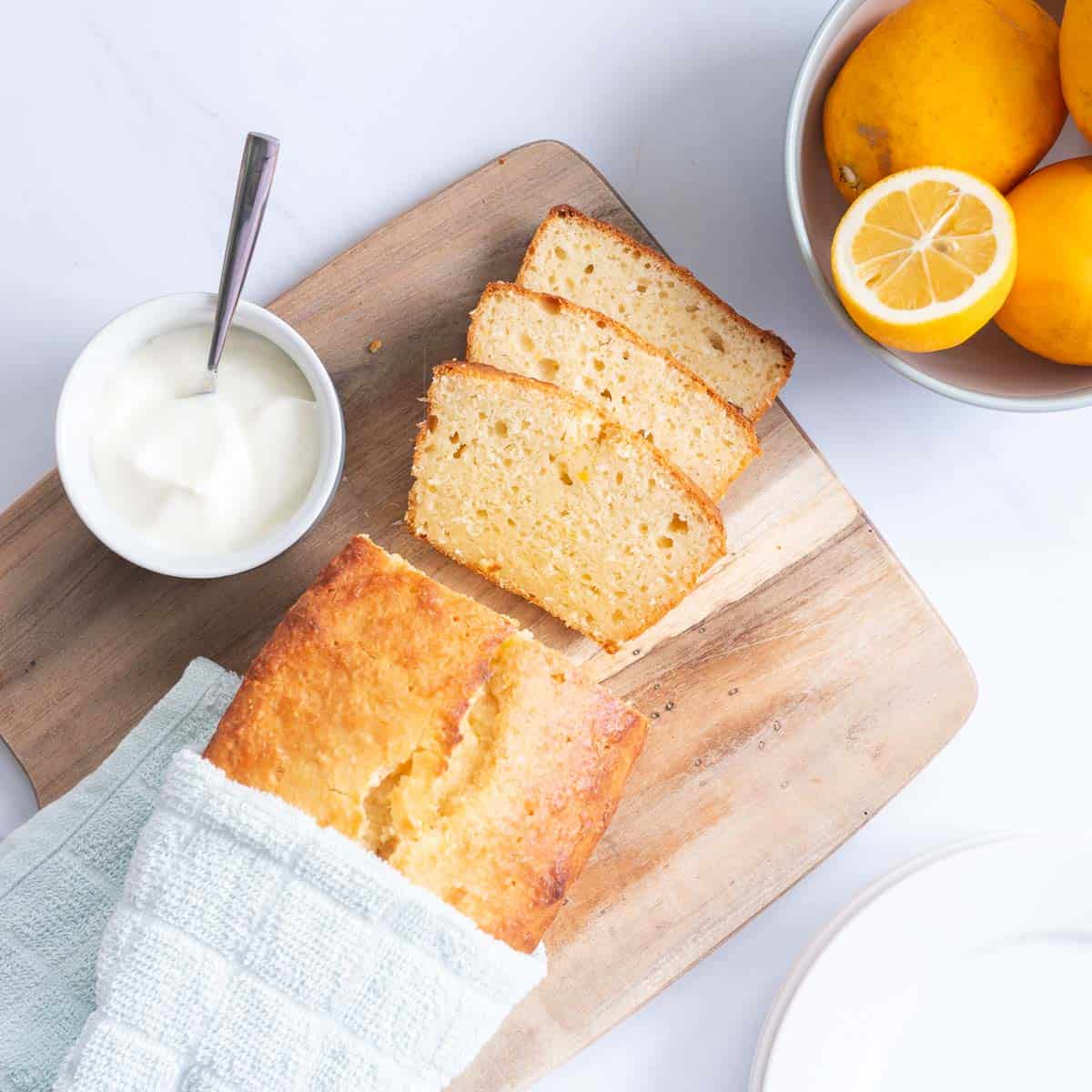 Lemon loaf on a wooding chopping board with a bowl of yoghurt and a bowl of lemons