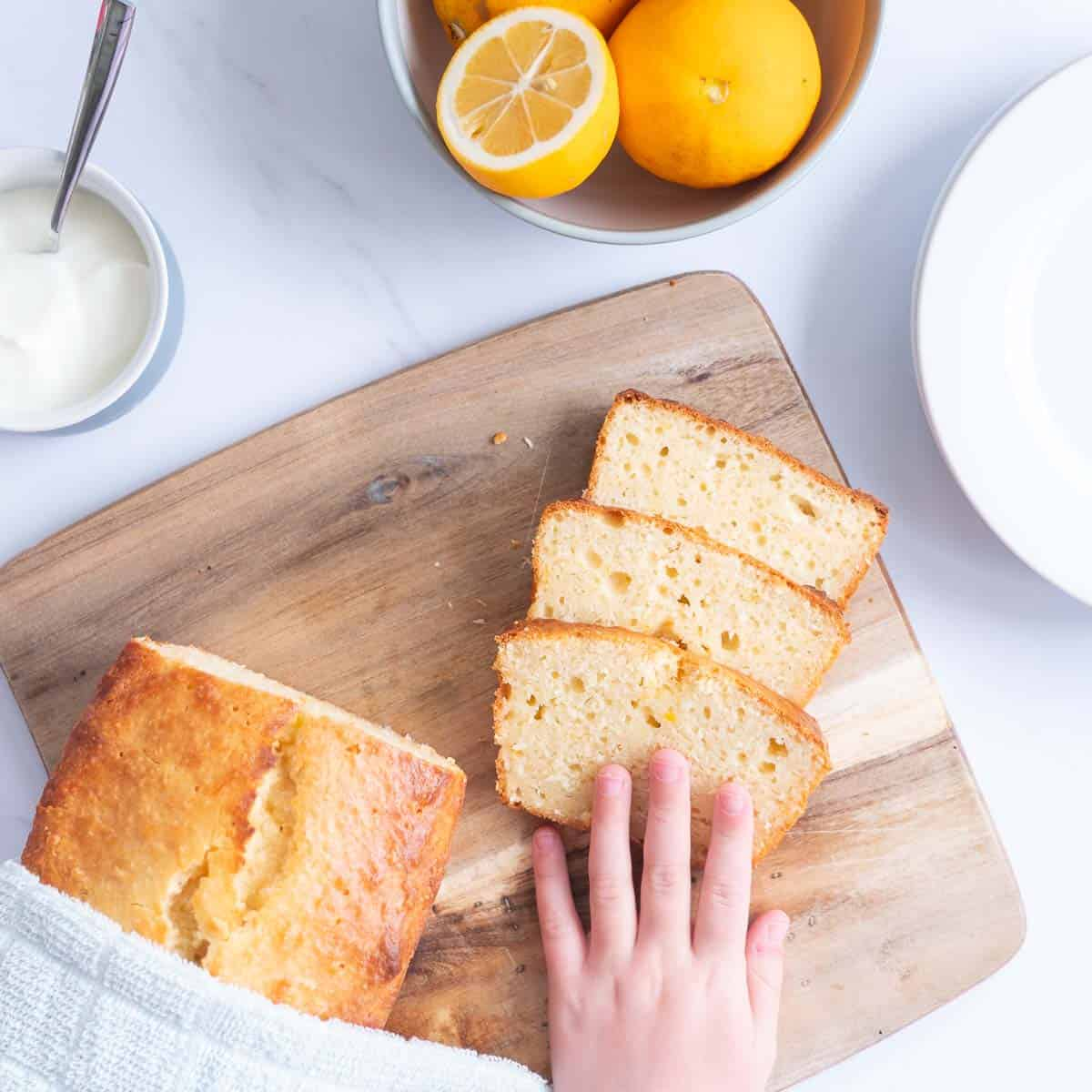 3 Slices of lemon loaf on a wooden chopping board with a child's hand reaching out for a piece