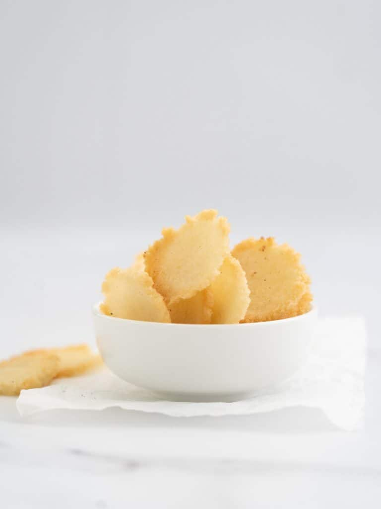 hoemade rice crackers in a white bowl on a marble bench top