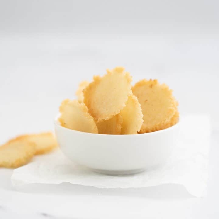 homemade rice crackers in a white bowl on a marble bench top
