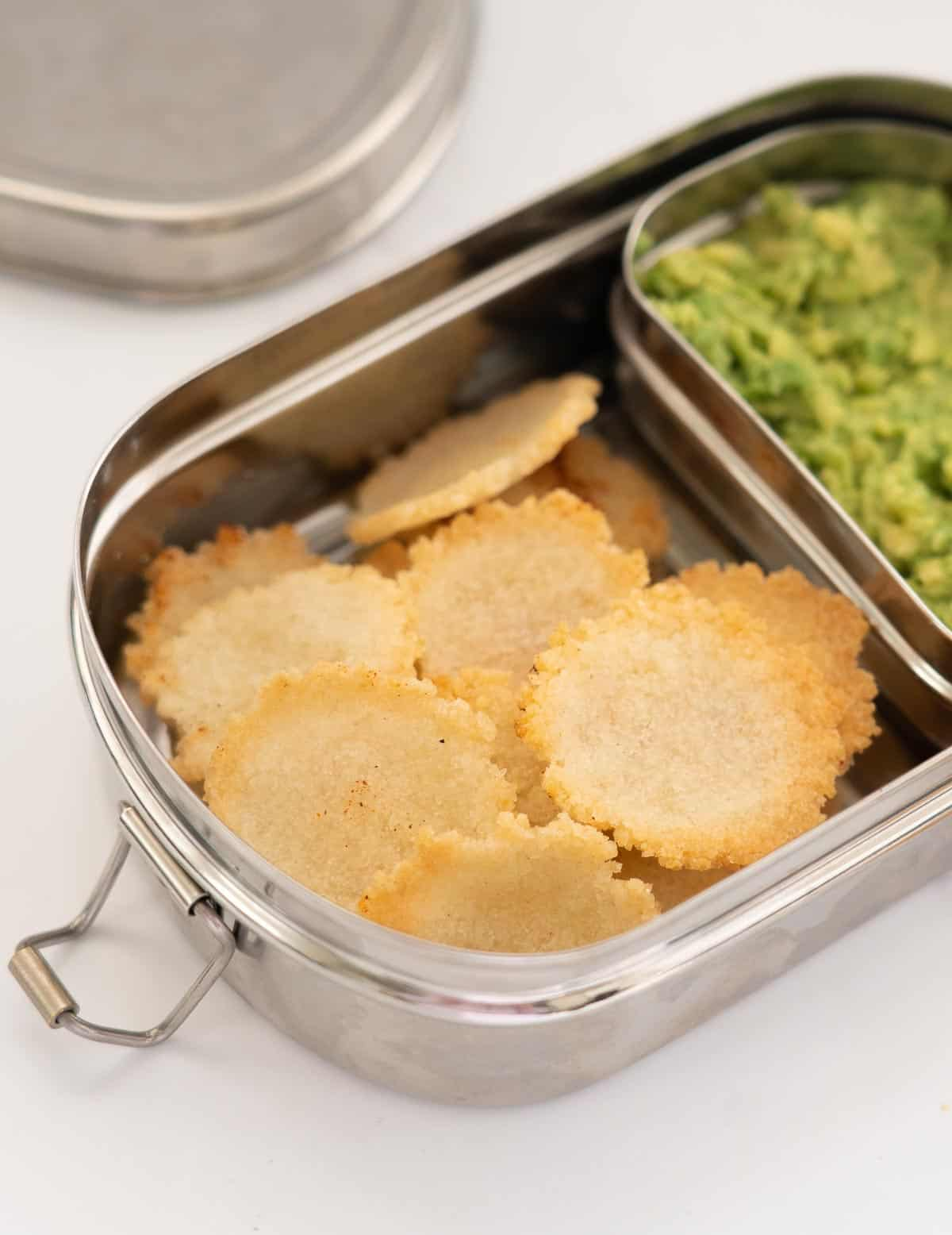 Rice crackers in a divided stainless steal lunch box with mashed avocado