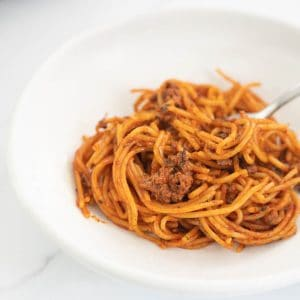 spaghetti bolognese in a white bowl with fork