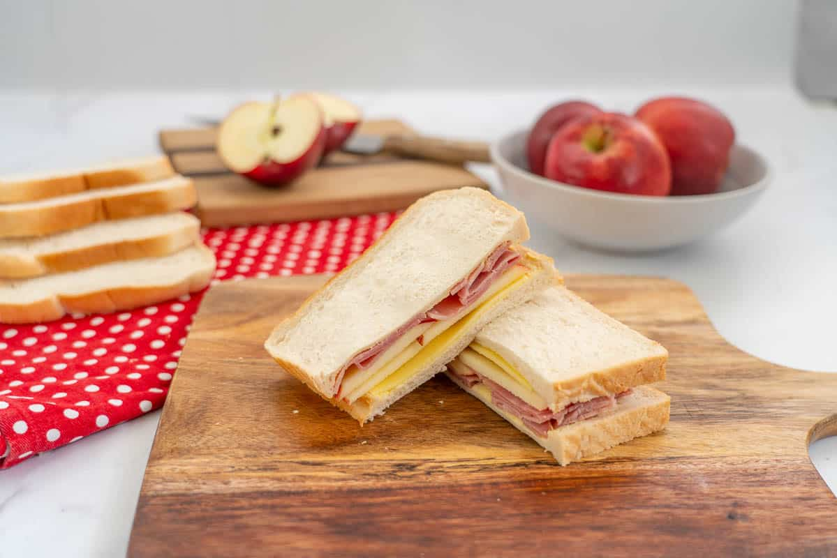 sandwich filled with apple, ham and cheese on a wooden chopping board