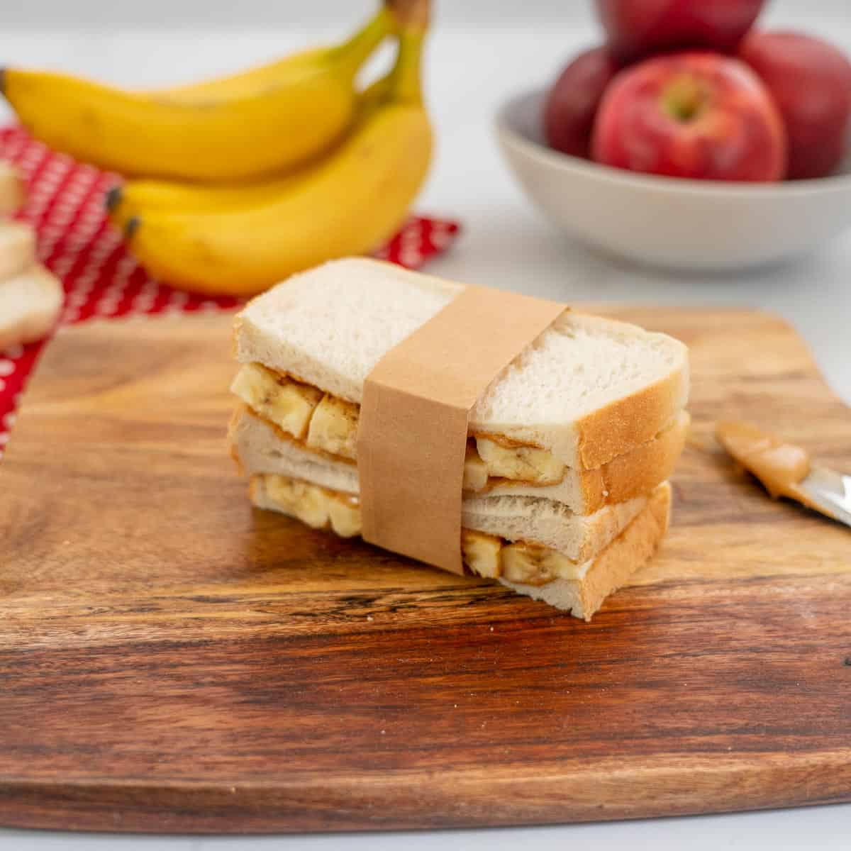 banana and peanut butter sandwich held together with a strip of brown paper