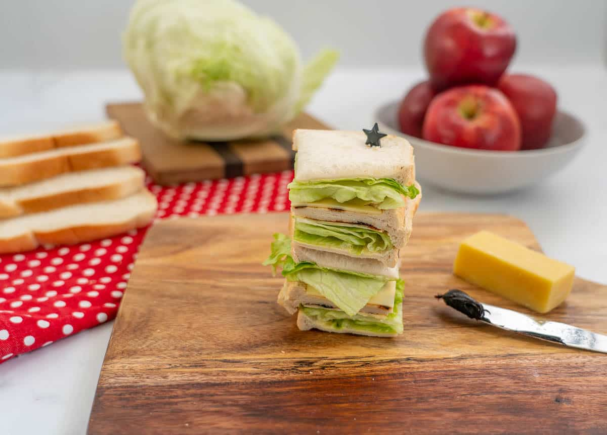 A stack of 4 small sandwiches filled with lettuce, cheese and marmit