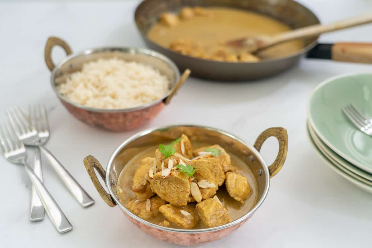 A bowl of chicken korma with rice in the background