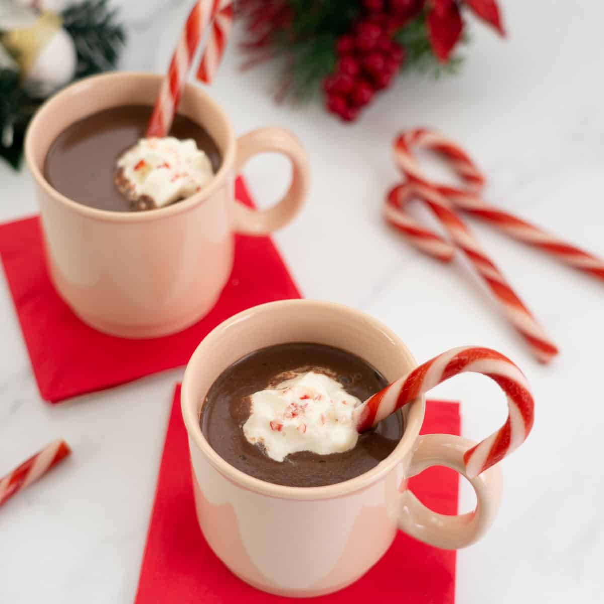 2 mugs of  hot chocolate topped with whipped cream, crushed candy canes and a candy cane to stir