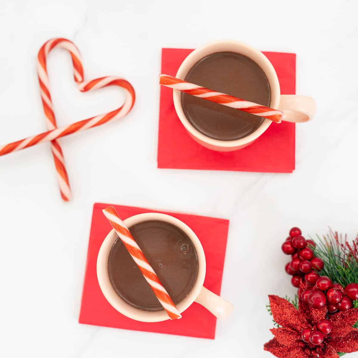 Top down view of 2 mugs of  hot chocolate on red napkins, decorated with candy canes.