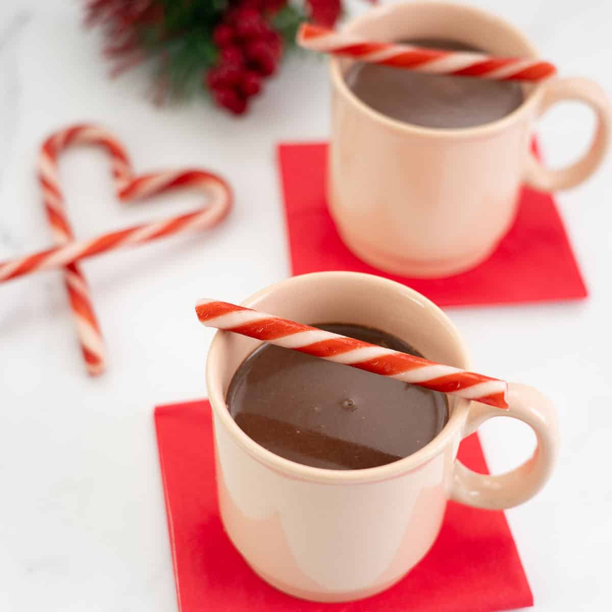 Two peppermint hot chocolates in pale pink mugs decorated with red and white candy canes