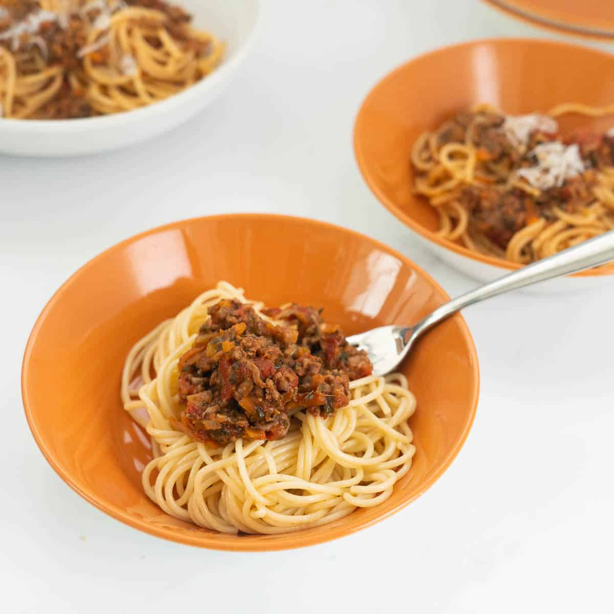 orange bowl filled with spaghetti and bolognese sauce