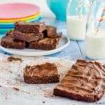 Pieces of chocolate slice on a blue table top with bottles of milk and straws.