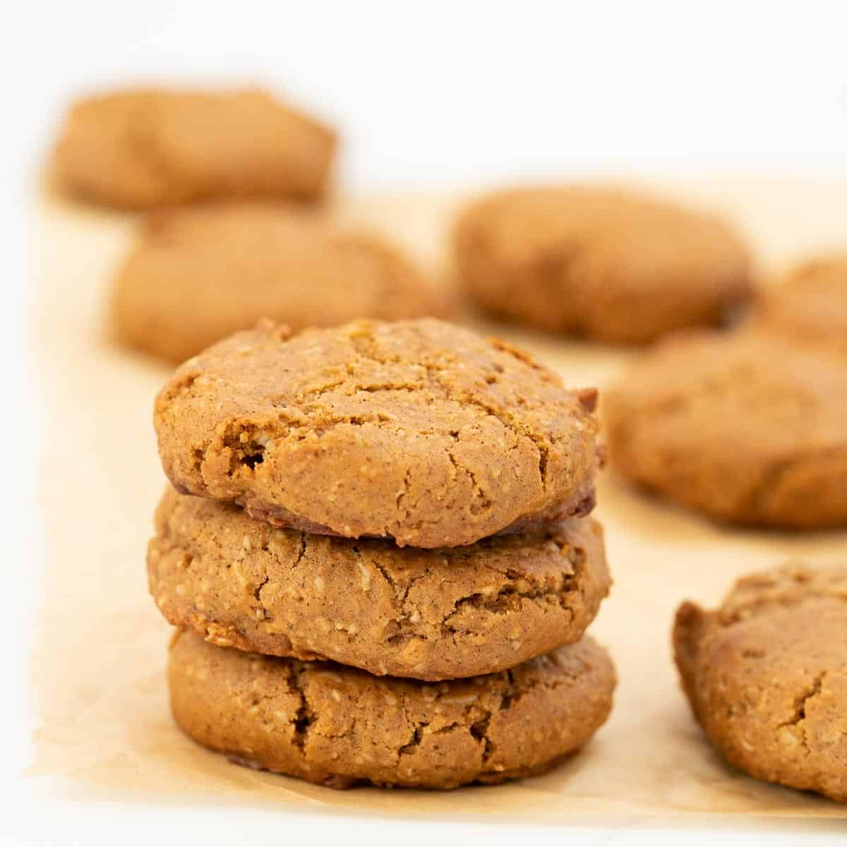 A stack of three cinnamon cookies sitting on parchment paper