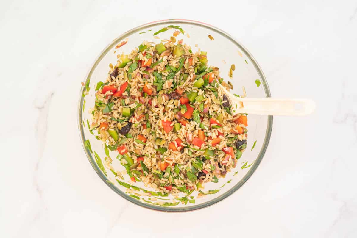 Large glass bowl filled with brown rice salad, red and green ingredients visible.