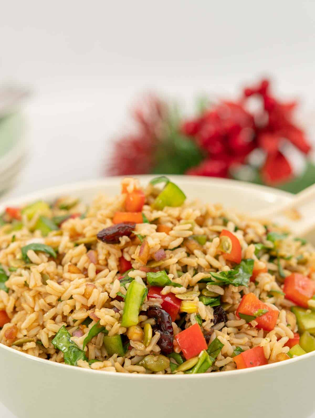 Close up of brown rice salad with red and green ingredients visible