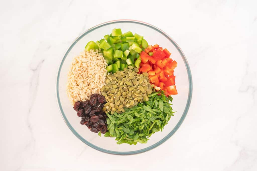 Large glass bowl of brown rice, capsicum, pumpkin seeds, cranberries and spinach