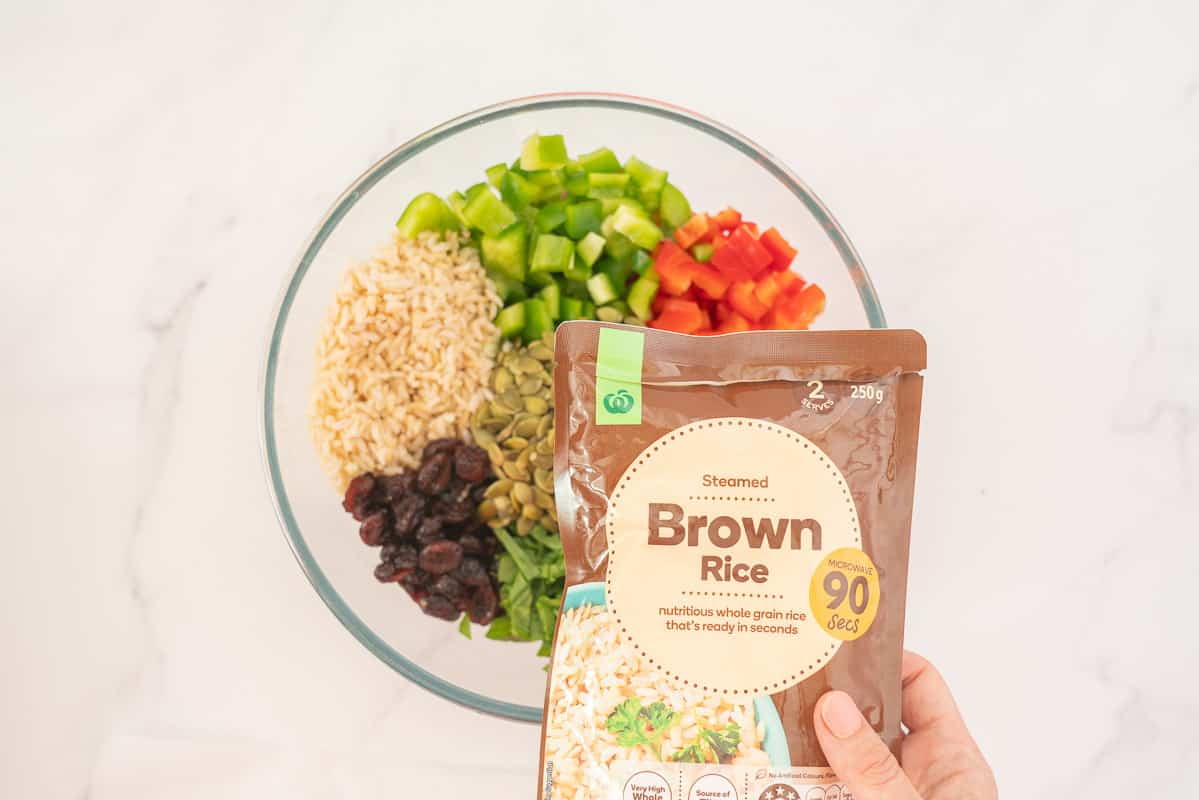 Woman's hand holding a pre-cooked brown rice package above a bowl of salad.