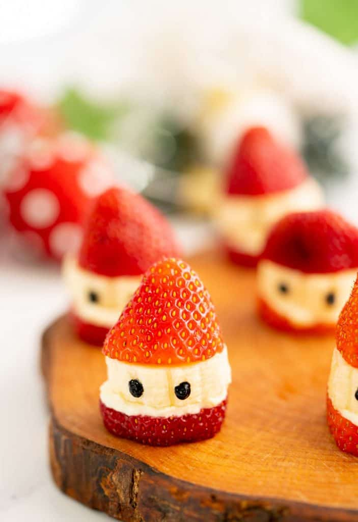 Strawberry Santas sitting on a wooden board.