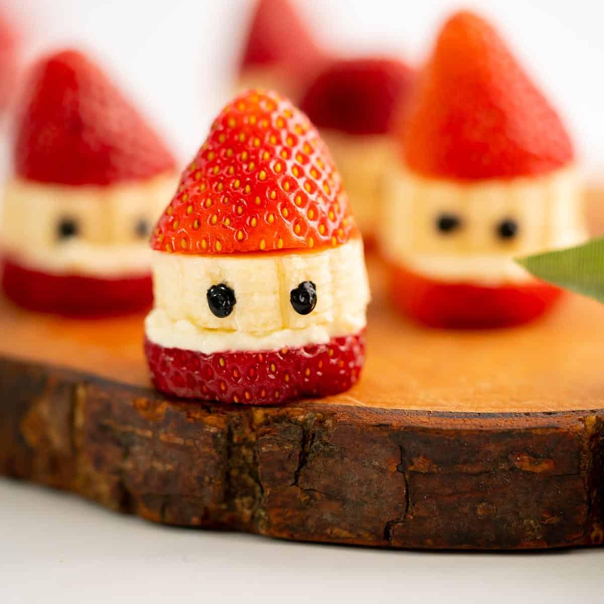 Strawberries, banana slices and cream cheese made to look like Santas.