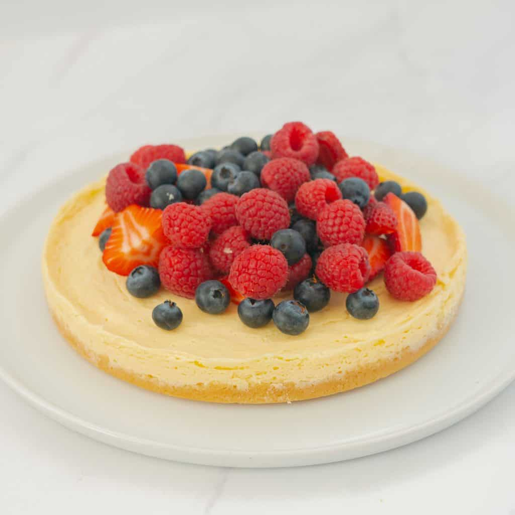 A round cheesecake with biscuit base topped with berries on a large white serving platter.