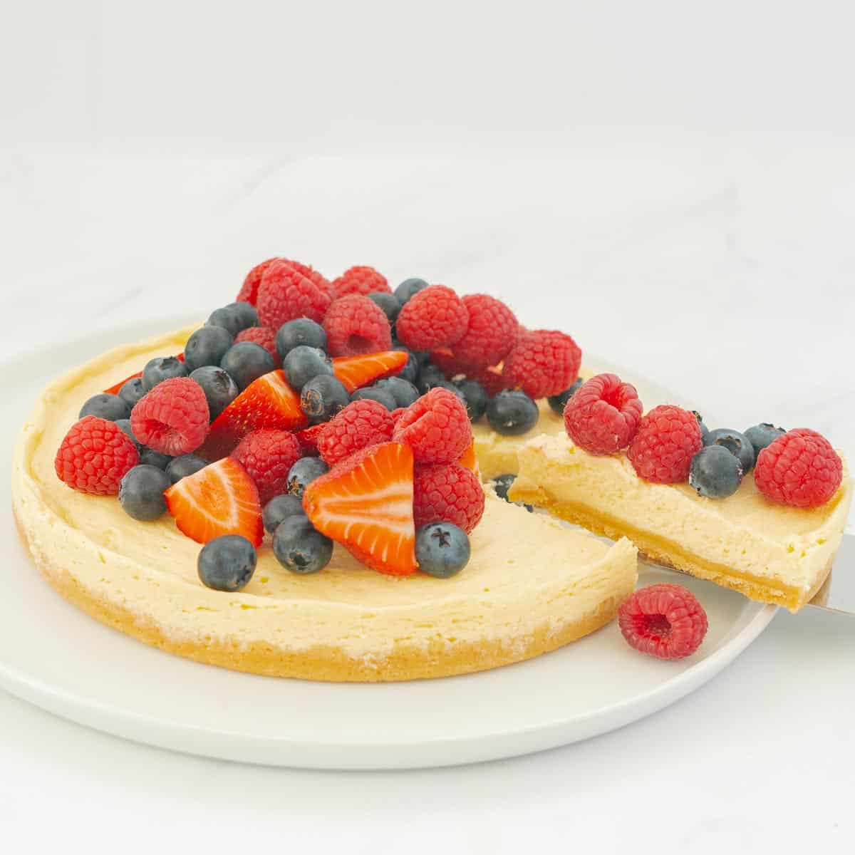 A round cheesecake with biscuit base topped with berries on a large white serving platter, a cake slice is removing one piece.
