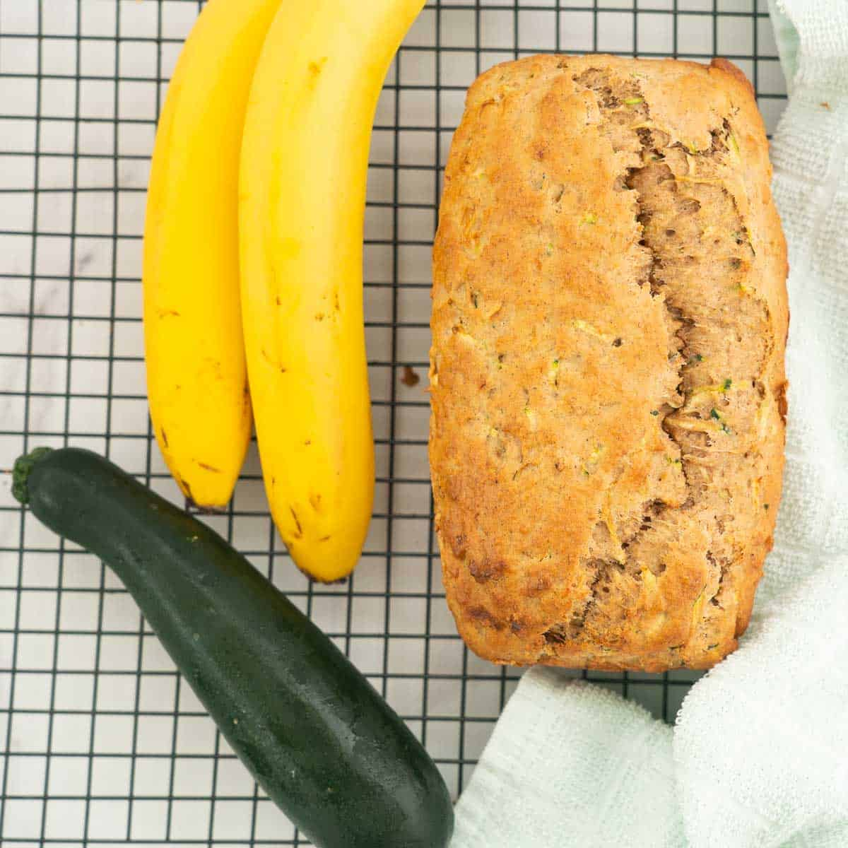 banana bread on a cooling rack with 2 bananas and a zucchini