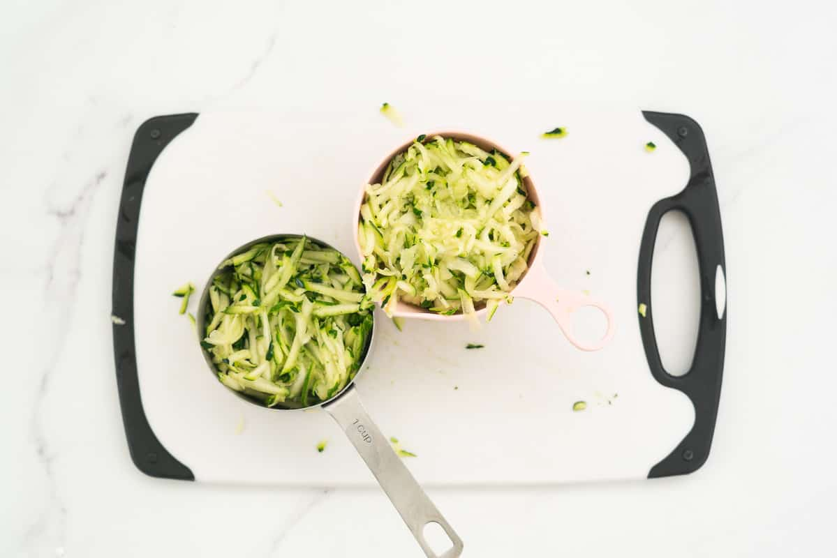 2 measuring cups of grated zucchini sitting on a white chopping board
