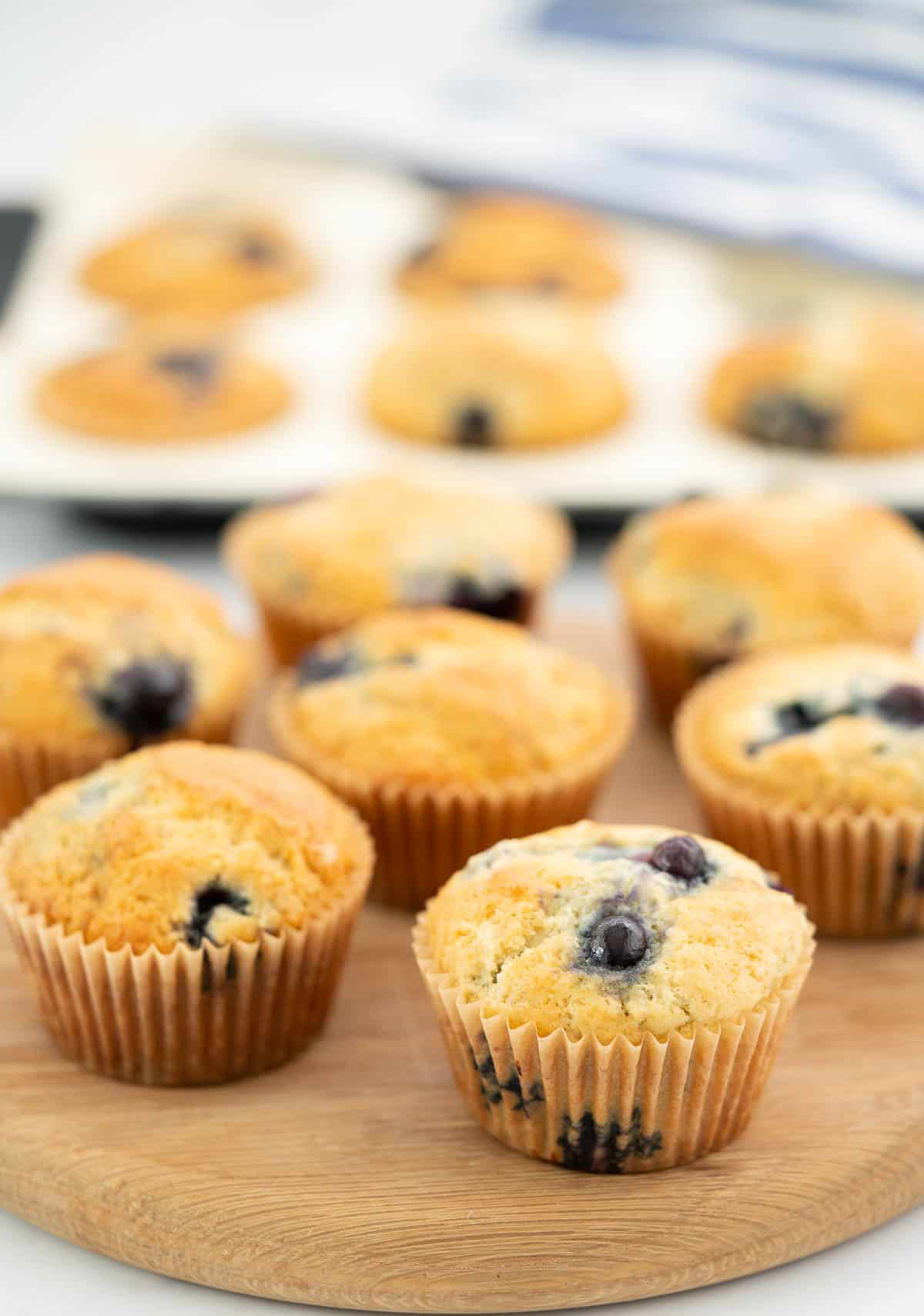 Blueberry studded muffins sitting on a circular wooden board.
