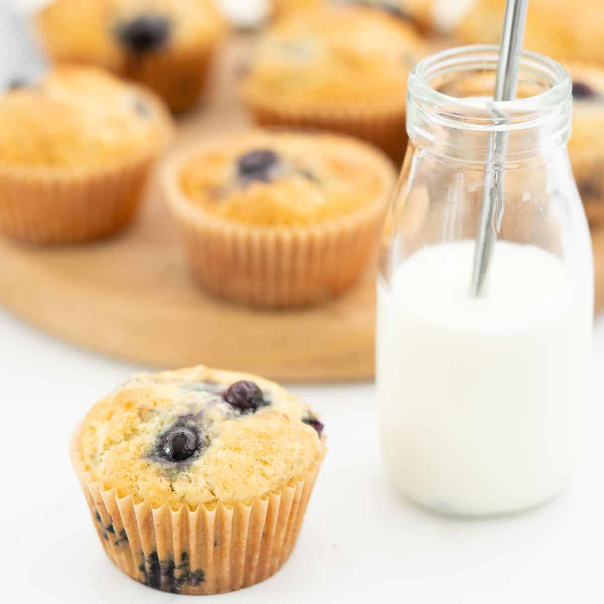 A blueberry muffin sitting next to a glass of milk with a straw.