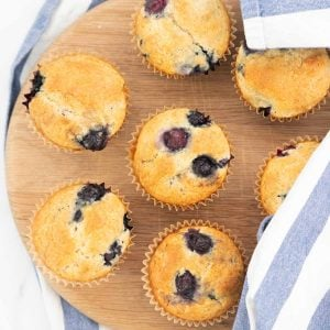 7 blueberry muffins on a round wooden chopping board, partly covered with a blue and white striped tea towel.