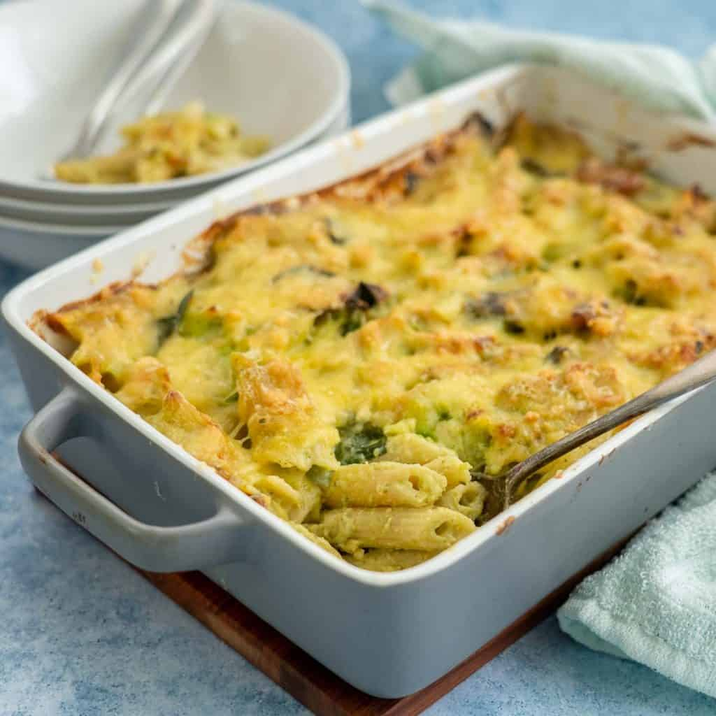 A slate blue rectangular ceramic baking dish filled with a cheesy chicken pasta bake