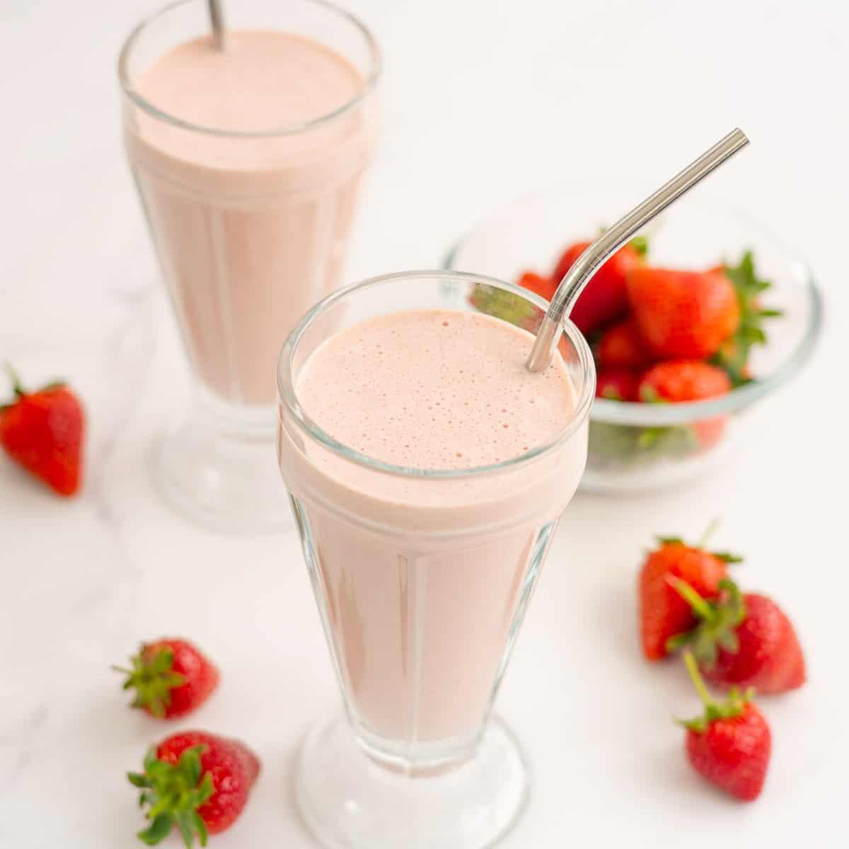 Two pink strawberry milkshakes in tall ice cream sundae glasses.