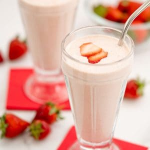 Two strawberry milkshakes in tall glasses topped with strawberry slice with red napkins.