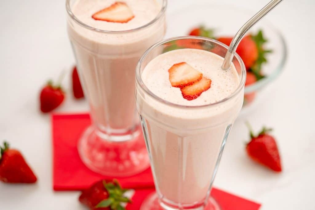 A close up of Two strawberry milkshakes in tall glasses topped with strawberry slice with red napkins.